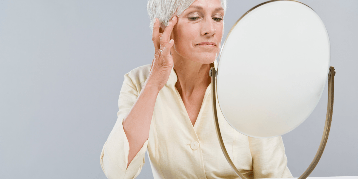 Older woman looking in the mirror touching skin care lines