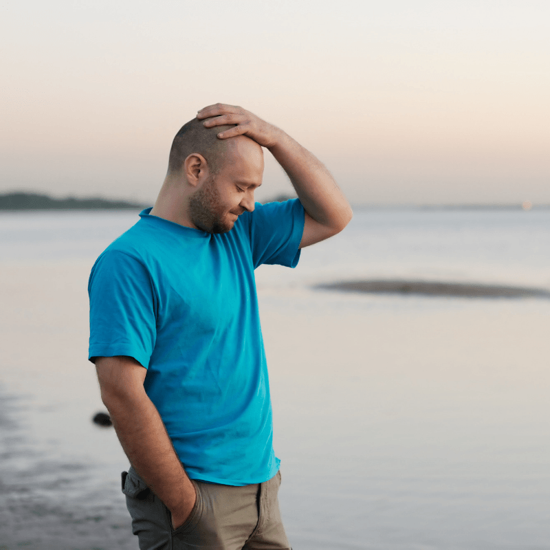 Balding man in blue t-shirt sadly holds his head