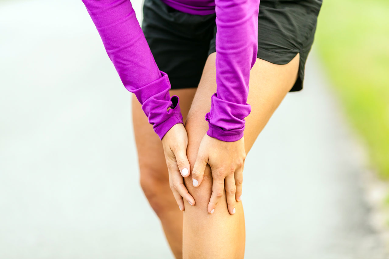 Woman holding her painful knee joint